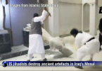 A video shows militants knocking sculptures off the walls of a building, shooting at them with an assault rifle and hacking away at a statue with a pickaxe.