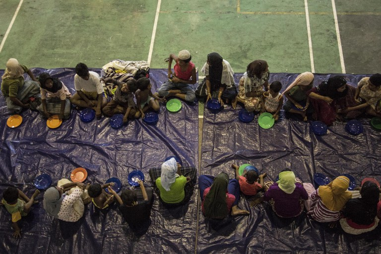 The boat people waiting for their meal at a sports hall in Lhoksukon, Aceh, after being rescued. -- AFP photo by Reza Juanda
