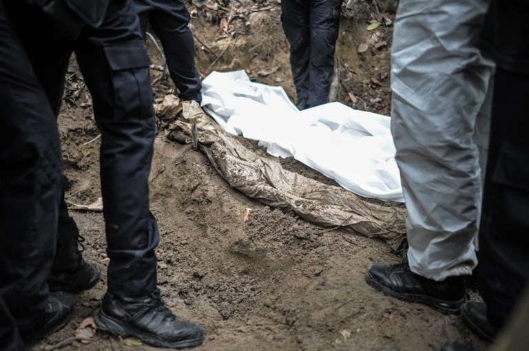 The white shroud covering the body (left) of the migrant found in the jungle camp in Wang Kelian suggests that the victim was given a proper Muslim burial. -- AFP photo by Mohd. Rasfan