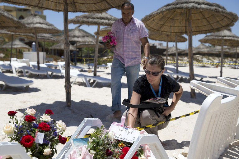 A couple lay flowers at the site of the massacre on the beach popular with foreign tourists.