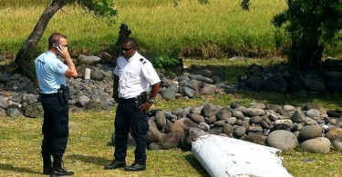 A policeman and a gendarme stand next to debris that is believed to be from a plane that was found on a beach on Reunion Island yesterday. -- AFP photo by Yannick Pitou.