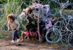 An immigrant family goes under the barbed fire on the Serbia-Hungary border to cross into the latter. -- AFP photo