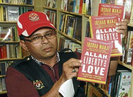 A New Straits Times photo of a Jawi officer holding the books that were taken during the raid at the Borders bookstore.