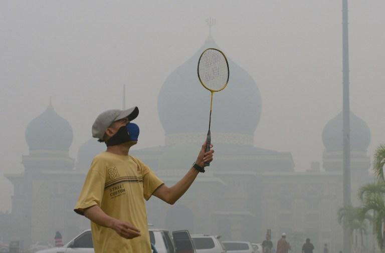 A man plays badminton outside a mosque in Pekanbaru, Riau, despite the thick haze enveloping the environment. -- AFP photo by Adek Berry.
