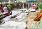 Emergency personnel and pilgrims stand next to bodies of victims of the stampede. -- AFP/STR photo