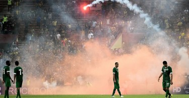 Saudi Arabia players remain on the pitch as a flare is thrown from the terraces. -- Photo by AFP/Getty Images.