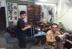 Cheong Chan Long (right) and son Patrick Cheong Choon Lam  repairing bags at their shop.