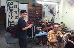 Cheong Chan Long (right) and son Patrick Cheong Choon Lam  repairing bags at their shop.