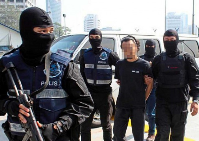 A Malaysian suspected of being involved in terrorism-related activities is taken away by police.