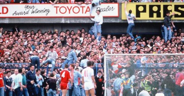 Fans being helped up to the higher terrace or over the fence onto the pitch to escape the crush.