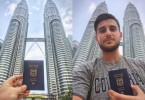 Rochman posing with his Israeli passport in front of Petronas Twin Tower.