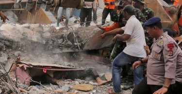 Another victim lies beneath the rubble.