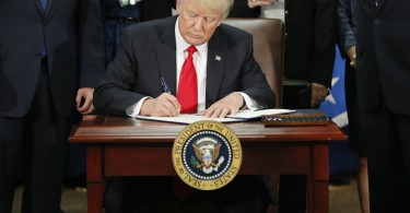 Trump the new president signing the order that has been soundly condemned around the world and also in his own country.