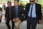 Ahmad Zukhairi (centre) being taken to the courtroom to be charged.