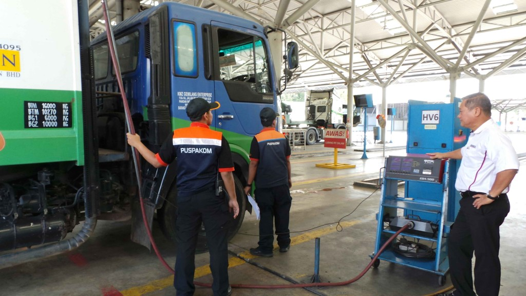 Ooi (right) supervising Puspakom's vehicle inspectors in an automated smoke emission test.