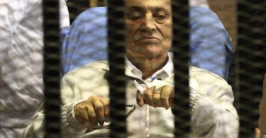 Egypt's ousted President Mubarak sits inside a dock at the police academy on the outskirts of Cairo