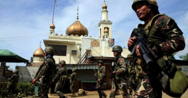 Filipino soldiers advancing past a mosque at Marawi City.