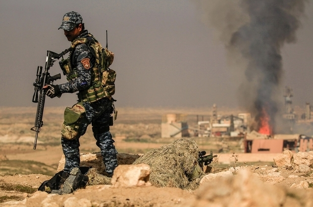 Smoke rises  from  sugar factory as Iraqi security forces sniper  aim his weapon toward Mosul's airport  during a battle  with islamic state's militants south west Mosul,