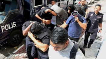 Some of the Bayan Baru cops hiding their faces from press cameras.