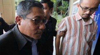 Azman (left) and Wardi being taken to court.