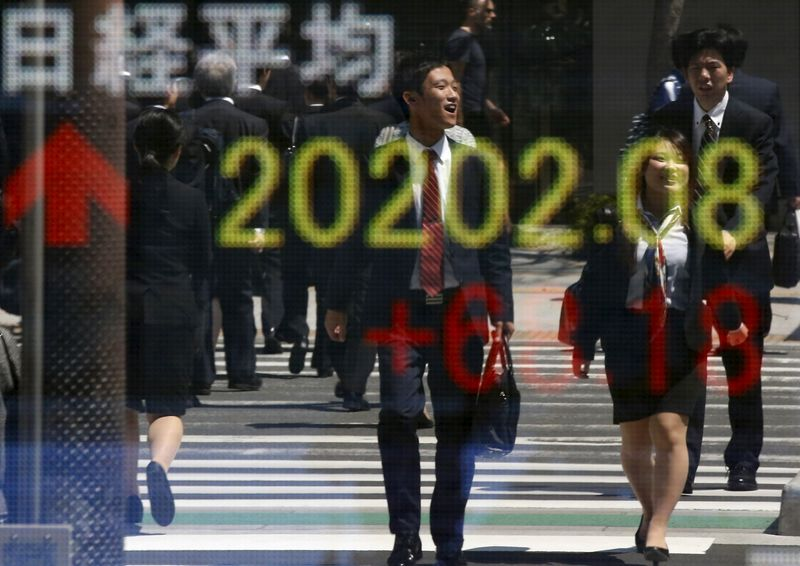 People are reflected in an electronic board displaying Japan's Nikkei share average outside a brokerage in Tokyo