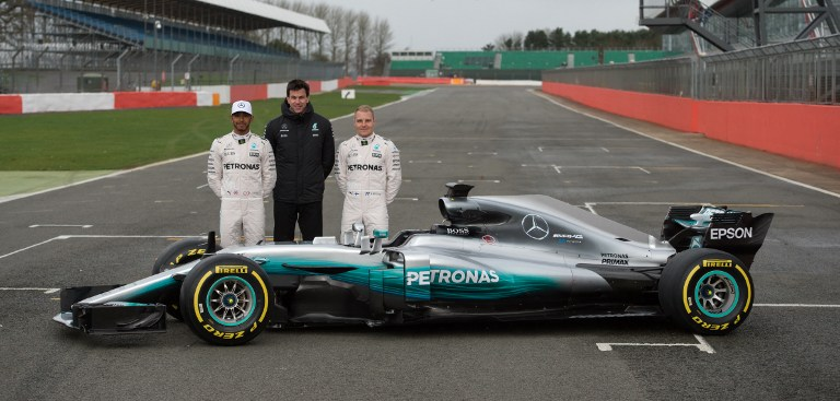 Mercedes AMG Petronas Formula One drivers Lewis Hamilton (L) and Valtteri Bottas (R) pose with Mercedes head Toto Wolff by the 2017 season Mercedes W08 EQ Power+ Formula One car at its launch event at Silverstone.