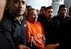 Isa (in orange shirt) is being remanded as part of the MACC's investigation into some transactions by a Felda subsidiary.