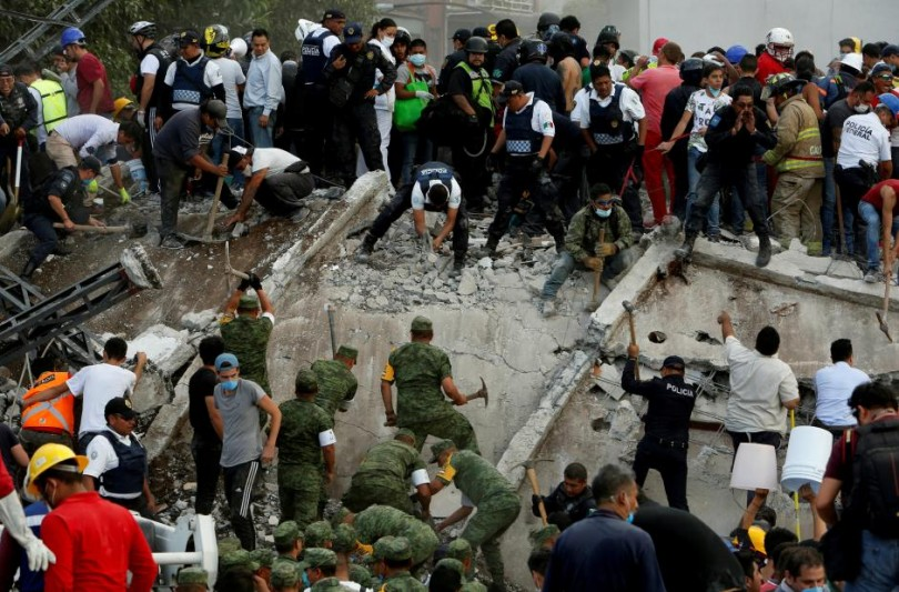 Soldiers, rescuers and people work at a collapsed building after the earthquake.