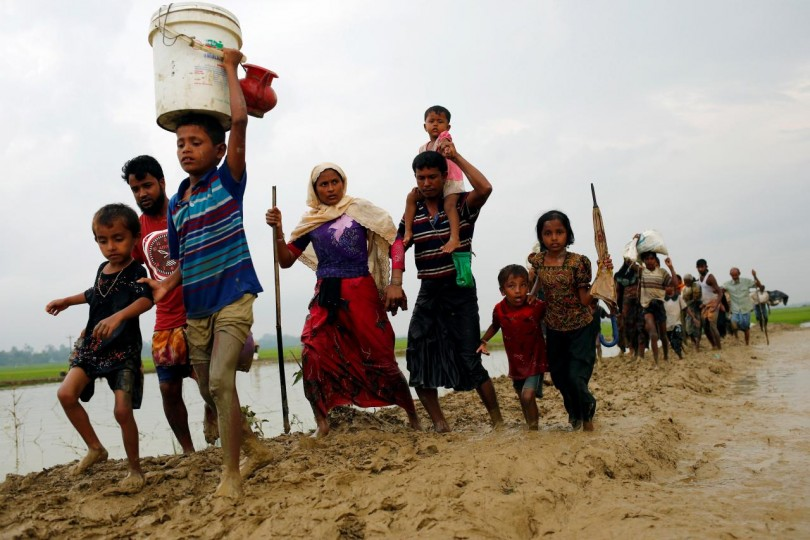 Rohingya refugees walk on the muddy path after crossing the Bangladesh-Myanmar border in Teknaf, Bangladesh .