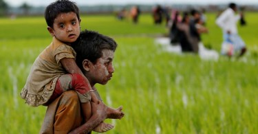 A Rohingya boy carries a child after crossing the Bangladesh-Myanmar border in Teknaf, Bangladesh on Friday.