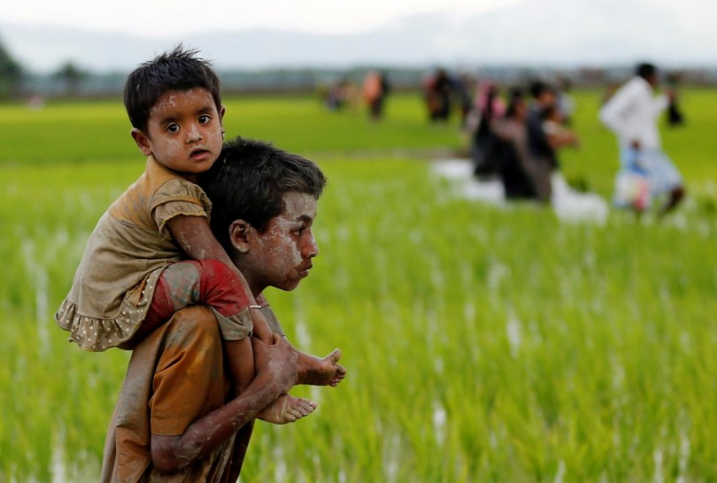 A Rohingya boy carries a child after crossing the Bangladesh-Myanmar border in Teknaf, Bangladesh on Friday.