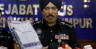 Kuala Lumpur police chief Datuk Amar Singh Ishar Singh holds up the belongings of a detained suspect  at the press conference