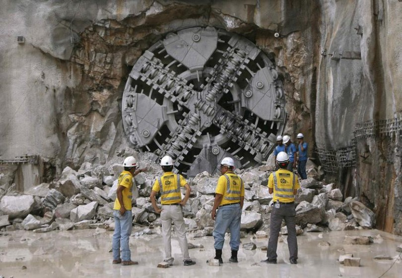 Engineers stand in front of a Tunnel Boring Machine (TBM) during the breakthrough of a tunnel in Kuala Lumpur January 10, 2014. The world's first variable density TBM has completed the first section of the 9.5km twin tunnels of the Klang Valley MRT.