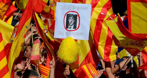 Anti-secession  demonstrator holds a placard bearing a crossed-out portrait of Catalan regional leader Carles Puigdemont during a demonstration on Sunday.