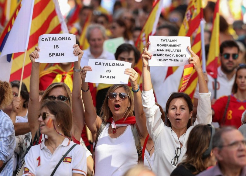 People hold up signs as they attend a pro-union demonstration organised by the Catalan Civil Society organisation in Barcelona
