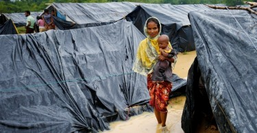 A Rohingya refugee woman and her child walk in floodwaters near makeshift shelters in Cox's Bazzar after heavy rain.