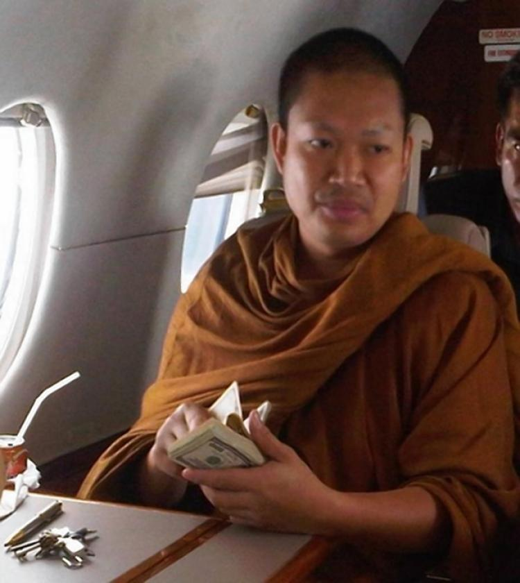 Wirapol Sukphol, a Thai Buddhist monk who had been outed for living a lavish life-style, is seen in a photo holding a wad of cash while riding aboard a private plane. The 33-year-old  monk had been implicated on charges including statutory rape, embezzlement and online fraud. He was extradited back to Thailand from United States in July.
