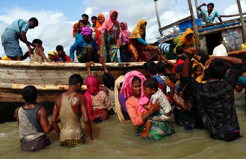 Rohingya refugees get off a boat after crossing the Bangladesh-Myanmar border through the Bay of Bengal, in Shah Porir Dwip