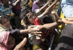 Desperate Rohingya refugees reach for aid handouts of clothing and food on Sept. 15,  in Tankhali, Bangladesh