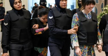 Siti Aisyah and Doan Thi Huong under police escort and wearing bulletproof jackets during the visit to the crime scene.