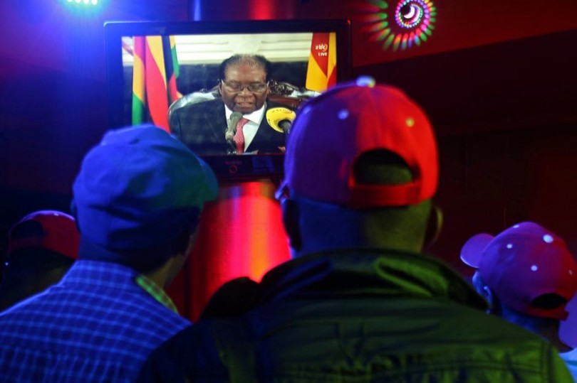 People watch as Zimbabwean President Robert Mugabe addresses the nation on television, at a bar in Harare yesterday.