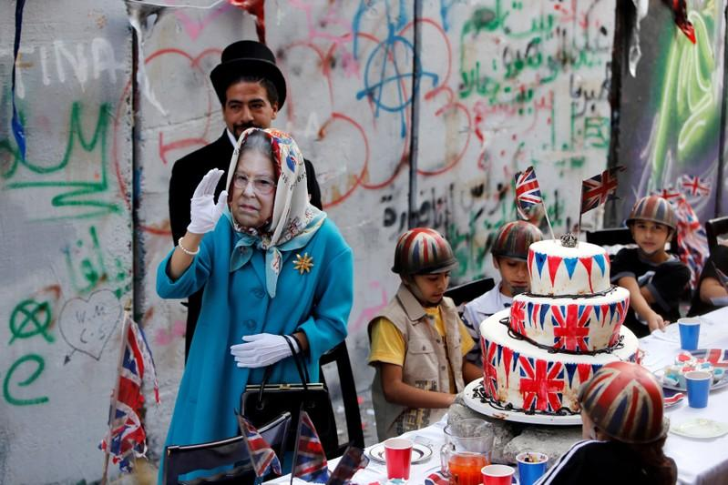 A person, dressed as Britain's Queen Elizabeth II, gestures during a tea party for Palestinian children to mark the anniversary of the Balfour Declaration, outside Banksy's Walled Off Hotel in the West Bank city of Bethlehem.