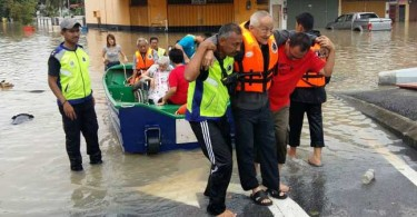 Rescuers assisting a senior citizen during the flood yesterday.