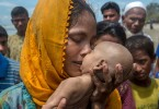 A Rohingya Muslim woman, Hanida Begum, who crossed over from Myanmar into Bangladesh, kisses her infant son, Abdul Masood, who died when the boat they were traveling in capsized just before reaching the shore of the Bay of Bengal, in Shah Porir Dwip, Bangladesh, on Sept 14 last year.