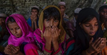 Rohingya Muslim girls, who crossed over from Myanmar into Bangladesh, pray at the end of their journey.