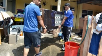 Volunteers help to clean up a flood victim's house in Taman Bertam Indah, Kepala Batas yesterday. - Picture courtesy of theSundaily