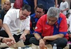 "Deputy Prime Minister Datuk Seri Ahmad Zahid Hamidi and Penang Chief Minister Lim Guan Eng eating ""nasi bungkus"" with flood victims during their rounds of relief centres yesterday."