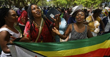 Zimbabweans celebrates near the parliament building in downtown Harare after Robert Mugabe's resignation.