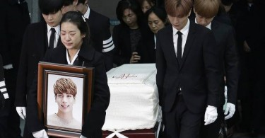 The coffin of Kim Jong-hyun being carried to a hearse by members of his band and other K-Pop stars.
