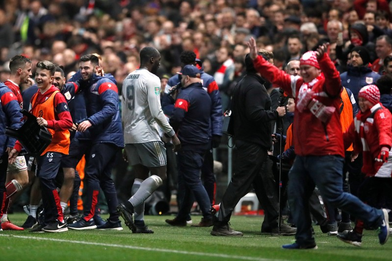 Manchester United's Romelu Lukaku looks dejected as he leaves the field whilst Bristol City players celebrate after the match .